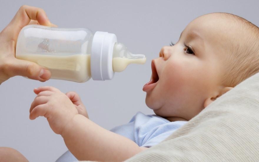 Ребенок пьет смесь с бутылочки